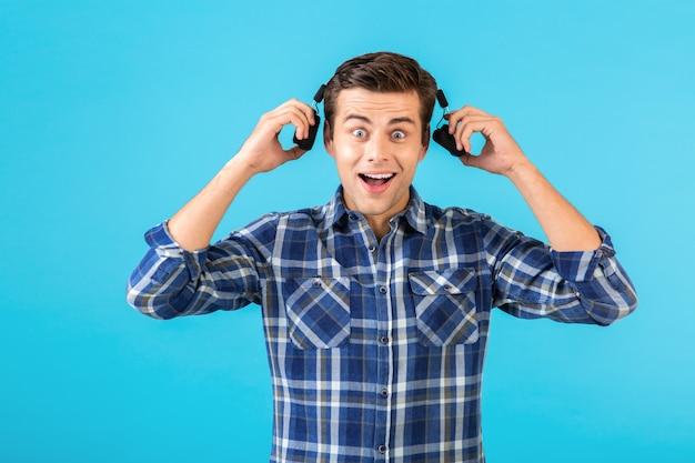 Stilvoller attraktiver hübscher junger mann, der musik auf kabellosen kopfhörern hört