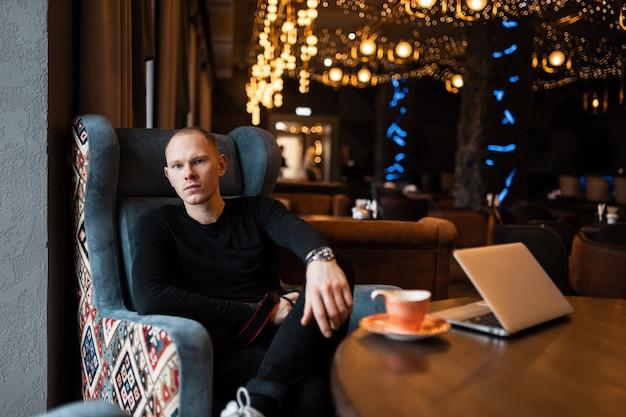 Stilvoller attraktiver junger mann in einem modischen hemd in stilvollen schwarzen jeans in turnschuhen sitzt auf einem sessel in einem restaurant