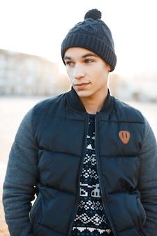 Stilvoller attraktiver junger mann in einer modischen mütze in einem blauen vintage-strickpullover in einer trendigen warmen winterjacke steht