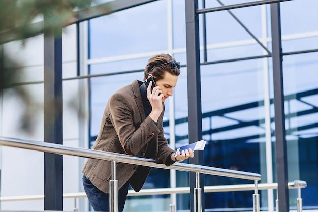 Stilvoller attraktiver kerl in der jacke mit telefonpass und karten
