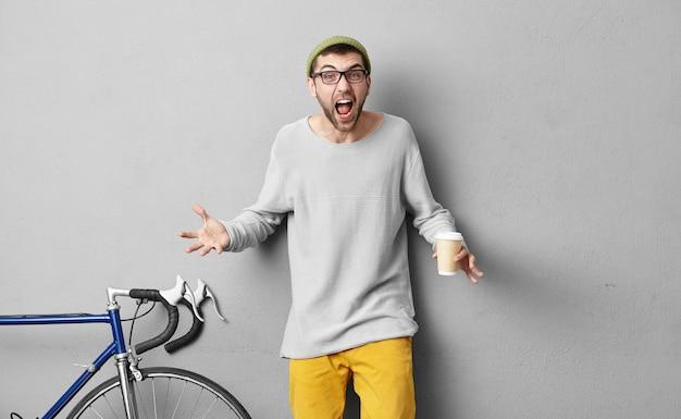 Stilvoller attraktiver mann, der streit mit seiner frau hat, während er seine wochenenden nicht mit ihr, sondern mit seinen besten freunden verbringt, kein fahrzeug für sie reparieren will, kaffee zum mitnehmen trinkt