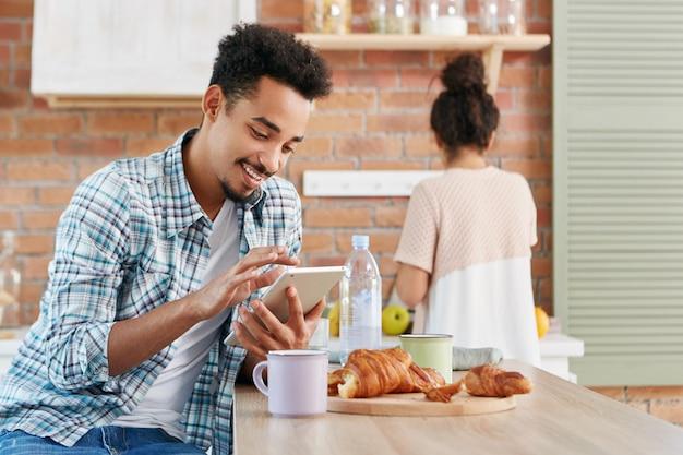 Stilvoller bärtiger gemischter afroamerikaner benutzt tablet-computer, schaut sich video oder film online an