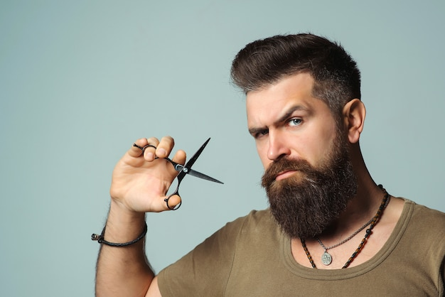 Stilvoller bärtiger mann. friseur hält schere. kleinunternehmen, friseurladen. hübscher friseur. herrenhaarschnitt, bartpflege. .