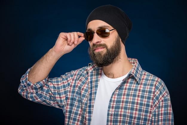 Stilvoller bärtiger mann in einer kappe und in den gläsern.