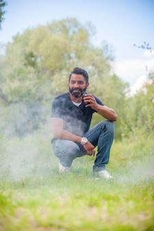 Stilvoller bärtiger mann mit elektronischer zigarette auf dem gras. konzept der elektronischen zigarette.
