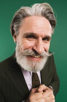 Stilvoller bärtiger mann mittleren alters im anzug hält hände nahaufnahme auf grüner wand zusammen