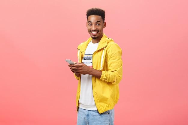 Stilvoller begeisterter afroamerikanischer mann mit afro-lockigem haarschnitt, der halb umgedreht über rosafarbene wand steht und smartphone mit gelber trendiger jacke trägt, die freudig lächelt und freundmerkmale des geräts zeigt.