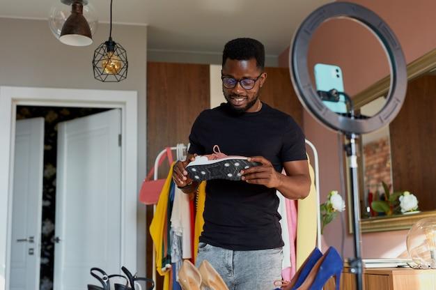Stilvoller bloggermann, der neue sportliche turnschuhe an der kamera prüft