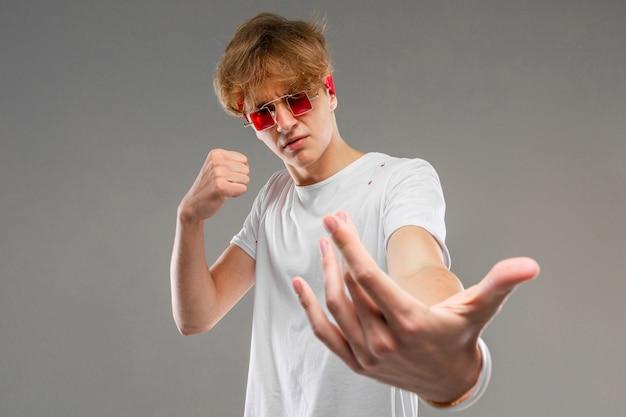 Stilvoller blonder kerl in der brille fordert einen showdown auf grauem hintergrund