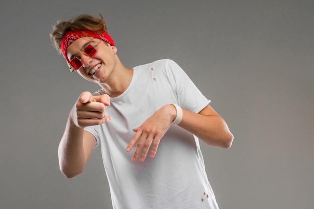 Stilvoller blonder typ mit einem kopftuch in brille und einem weißen t-shirt zeigt einen finger auf eine graue wand