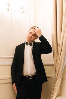 Stilvoller bräutigam, der anzug und fliege anzieht. selbstbewusstes und glückliches porträt des menschen. der bräutigam macht sich morgens fertig. kreatives hochzeitsfoto