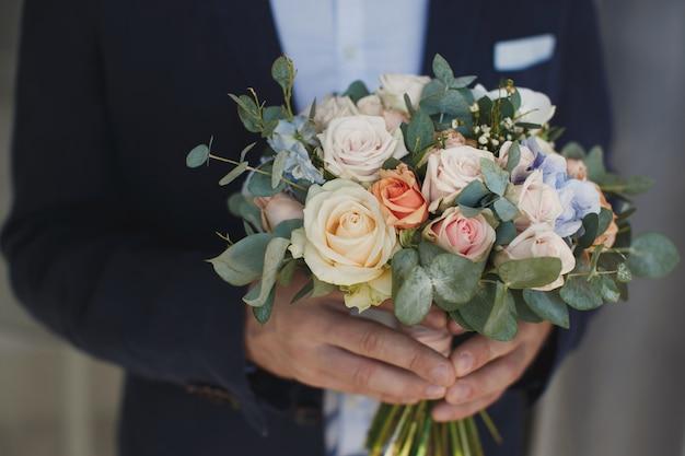 Stilvoller bräutigam, der einen zarten rosa hochzeitsstrauß hält