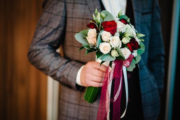 Stilvoller bräutigam halten brautstrauß. hochzeitsstrauß in mannhänden.