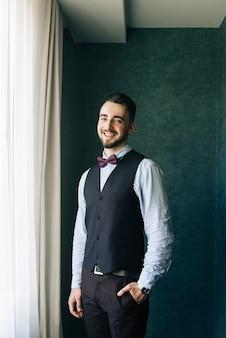 Stilvoller bräutigam im weißen hemd und in der fliege, die am fensterlicht aufwirft