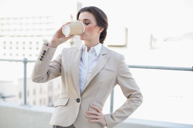 Stilvoller brauner behaarter trinkender kaffee der geschäftsfrau