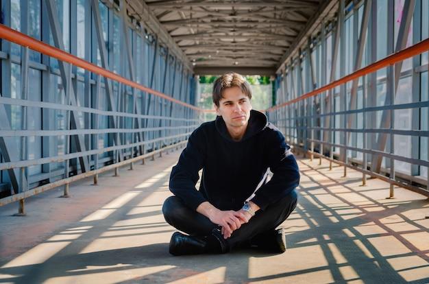 Stilvoller brünetter kerl in einem schwarzen sweatshirt im tunnel eines peschetodnogo übergangs.