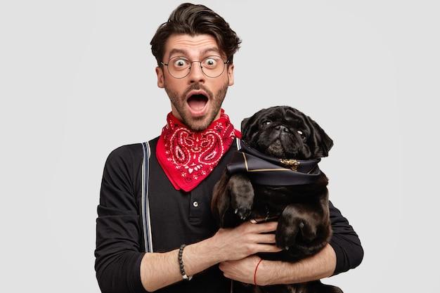 Stilvoller brunetmann, der roten bandana hält hund hält