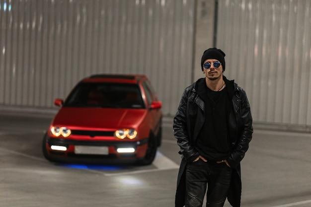 Stilvoller brutaler junger gutaussehender kerl mit sonnenbrille in modischer schwarzer kleidung mit lederjacke und hoodie geht nachts auf einem parkplatz in der nähe eines roten autos. urbaner männlicher casual-style