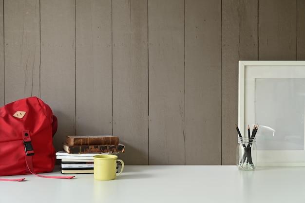 Stilvoller dachbodenarbeitsplatz mit leerem rahmen des modellmodells und innenministeriumgerät auf schreibtischtabelle.