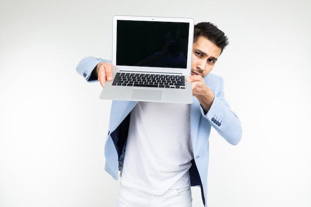 Stilvoller erfolgreicher mann in einer jacke demonstriert einen laptopbildschirm mit platz für werbung auf einem weißen studiohintergrund