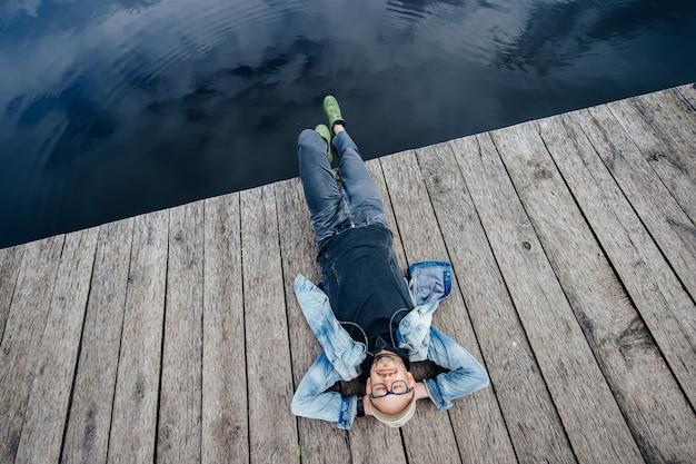 Stilvoller erwachsener mann, der auf altem hölzernem pier über see hinaus liegt. träumen des glücklichen bärtigen hippies im glasporträt von oben.