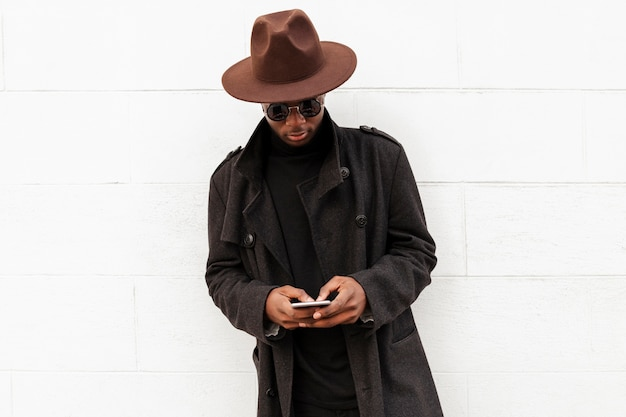 Stilvoller erwachsener mann, der mit hut und sonnenbrille aufwirft
