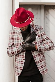 Stilvoller erwachsener mann mit schwarzen handschuhen und hut