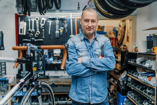 Stilvoller fahrradmechaniker, der in seiner werkstatt steht.