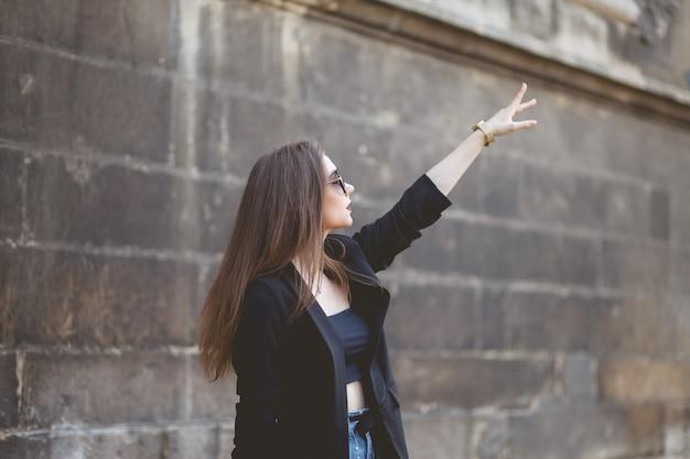 Stilvoller frauentourist zeigt einen finger auf die stadtanziehungskraft