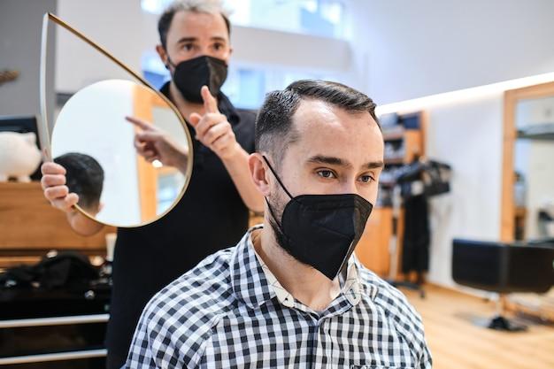 Stilvoller friseur, der die haare eines kunden in einem friseurladen schneidet.