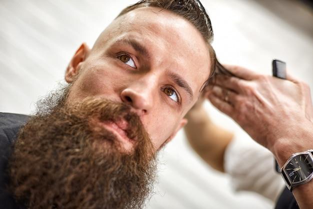 Stilvoller friseur schneidet einen brutalen mann mit einem dicken bart.