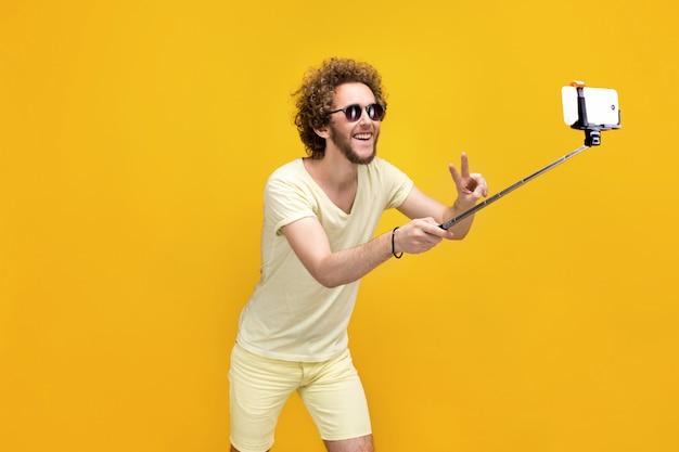 Stilvoller gelockter behaarter mann, der selfie mit einbeinstativ nimmt