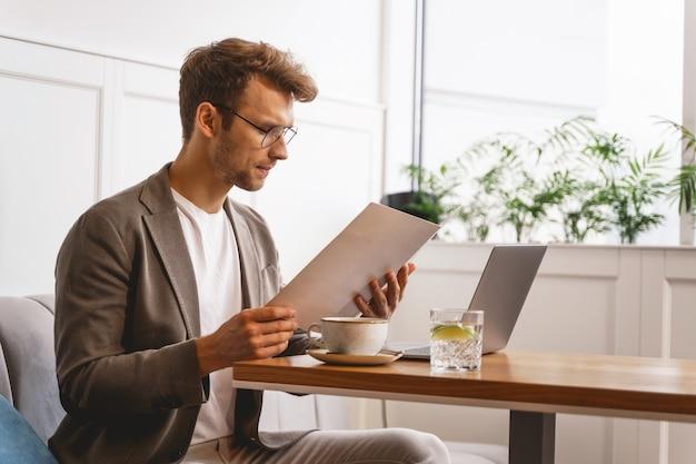 Stilvoller gentleman, der essen beim sitzen am café-tisch mit modernem laptop und tasse kaffee wählt