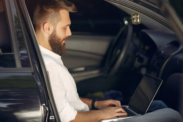 Stilvoller geschäftsmann, der in einem auto sitzt und den laptop benutzt