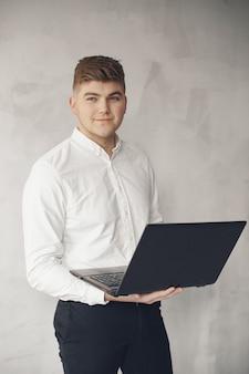 Stilvoller geschäftsmann, der in einem büro arbeitet und den laptop benutzt