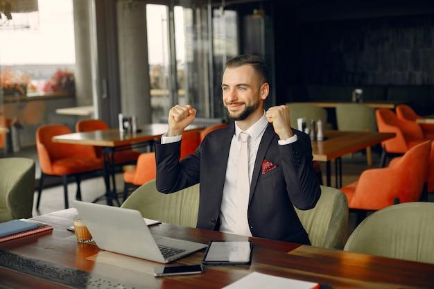 Stilvoller geschäftsmann, der in einem café arbeitet