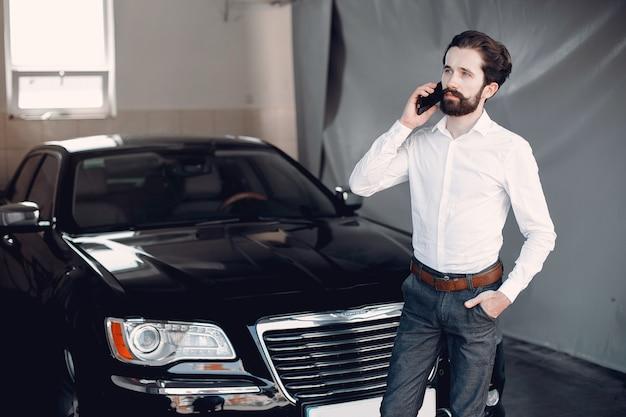 Stilvoller geschäftsmann, der nahe dem auto arbeitet