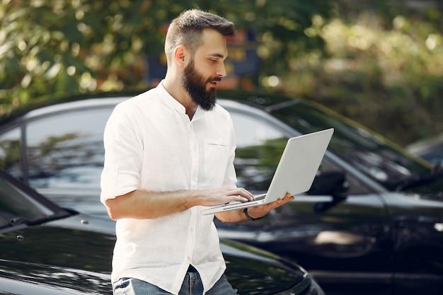 Stilvoller geschäftsmann, der nahe dem auto steht und den laptop benutzt