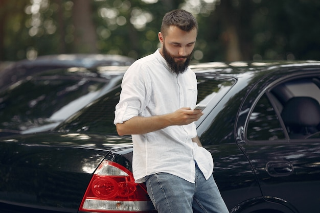 Stilvoller geschäftsmann, der nahe dem auto und dem gebrauchshandy steht