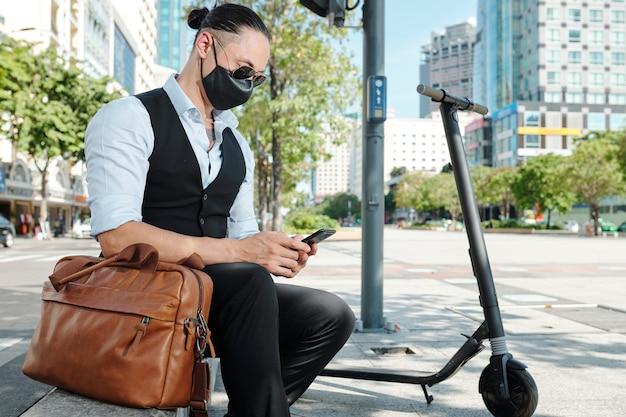 Stilvoller geschäftsmann in der stoffgesichtsmaske, die auf brüstung ruht, nachdem er auf roller gefahren ist und textnachrichten in seinem smartphone überprüft