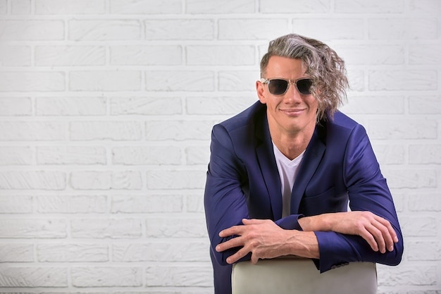 Stilvoller geschäftsmann mit dem gelockten langen haar in der sonnenbrille, die auf stuhl auf weiß sitzt