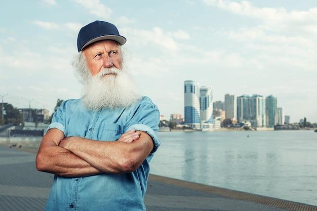 Stilvoller grauhaariger alter mann mit bart für einen spaziergang. glückliches gesundes alter.