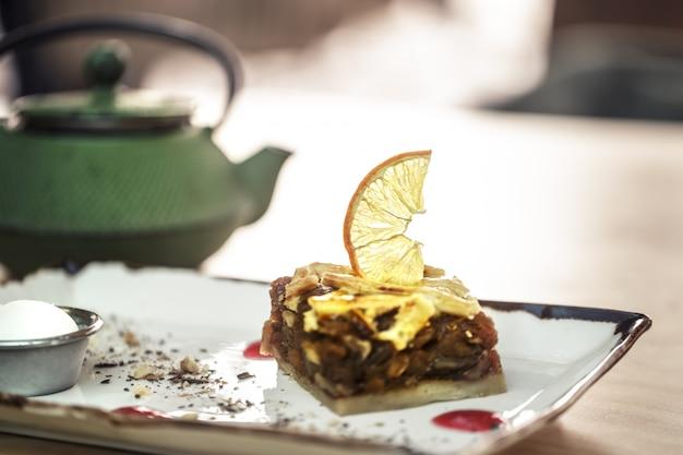 Stilvoller grüner wasserkocher mit tee und süßem dessert. karamellisierter apfelkuchen mit zitrone und kaltem eis