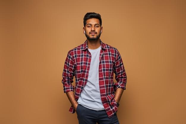 Stilvoller gutaussehender indischer mann im t-shirt auf pastellfarbener wand