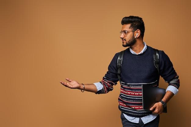Stilvoller, gutaussehender indischer student mit laptop und rucksack, der seine hand zur wand zeigt.