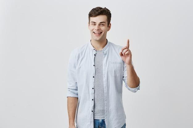 Stilvoller gutaussehender mann mit ansprechenden blauen augen, die in die kamera mit erfreutem ausdruck lächeln, der mit zeigefingern auf leerzeichen über kopf für ihren werbeinhalt zeigt. werbekonzept.