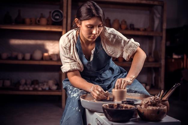 Stilvoller handwerker demonstriert den prozess der herstellung von keramikgeschirr mit der alten technologie