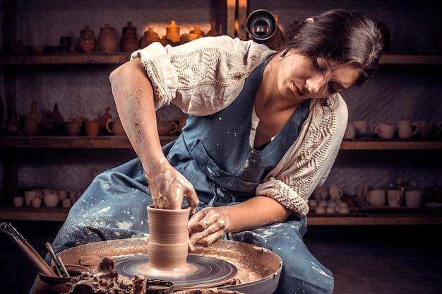 Stilvoller handwerker, der aufstellt, während er steingut macht. konzept für frau in freiberuflicher, geschäftlicher, hobby.