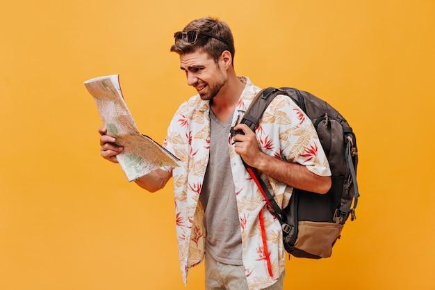 Stilvoller heller mann mit sonnenbrille in weiß bedruckter kleidung, der einen großen rucksack hält und auf die karte auf der orangefarbenen wand schaut