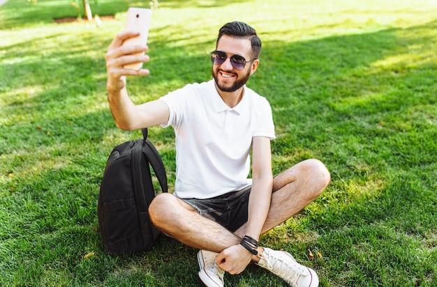Stilvoller hipster in einem weißen hemd sitzt auf dem rasen im park und macht ein selfie auf ihrem smartphone